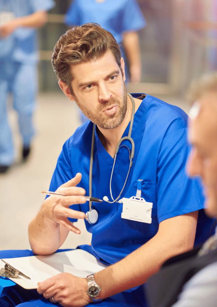 Male doctor in blue uniform talking to patient